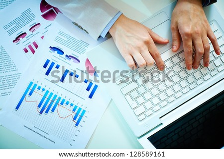 Close-up of female hands pushing laptop buttons - stock photo