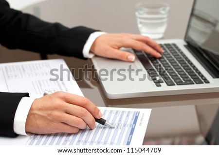 Close up of female hands reviewing accounting documents  on table.