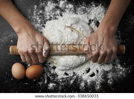 Close-up of female hands rolling dough with pin on wooden table. Concept of cooking and homemade meal.  - stock photo