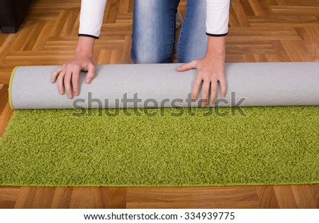 Close up of female hands rolling green fluffy carpet for cleaning - stock photo