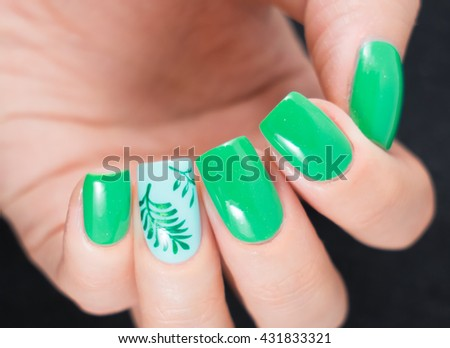 Close up of female hands showing colorful nail polish on black background. the woman is wearing green manicure. - stock photo
