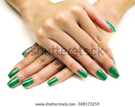 Close up of female hands showing colorful nail polish on white background.  the woman is wearing green manicure. - stock photo