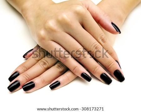 Close up of female hands showing colorful nail polish on white background.  The woman is wearing black manicure. - stock photo