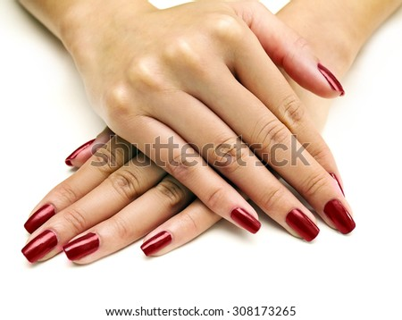 Close up of female hands showing colorful nail polish on white background. The woman is wearing red manicure. - stock photo