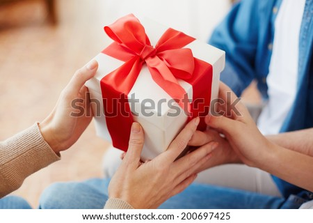 Close-up of female hands taking giftbox - stock photo