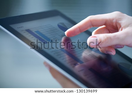 Close-up of female hands touching digital tablet with business diagram - stock photo