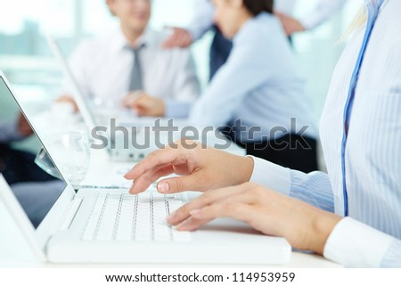 Close-up of female hands typing on the laptop keyboard in working environment - stock photo