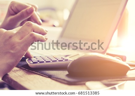 Close-up of female hands using laptop computer, working on laptop with flare light background. Searching Internet ,Businesswoman working at home office