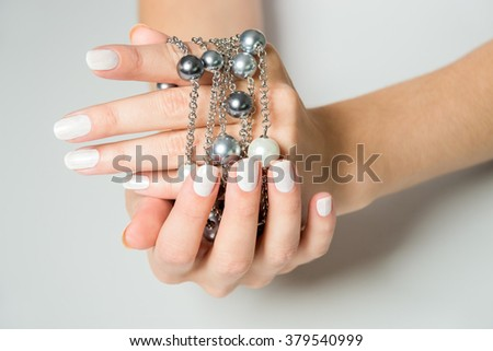 Close Up of Female Hands Wearing White Nail Polish with Silver Chain Necklaces with Gray Pearls Draped Over Sides with Gray Background and Copy Space - stock photo