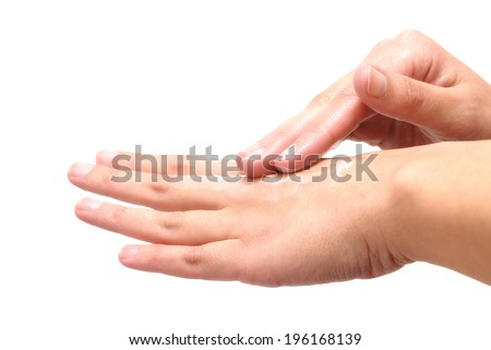 Close-up of female hands while applying moisturizing lotion in order to repair damaged and dry skin, on white background