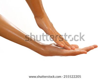 Close-up of female hands while applying oil on white background view 3 - stock photo
