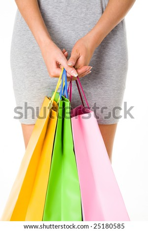 Close-up of female hands with colorful paperbags on background of her dressed figure - stock photo