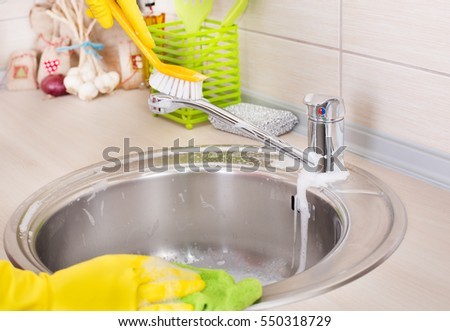 Close up of female hands with protective gloves scrubbing and cleaning kitchen faucet and sink