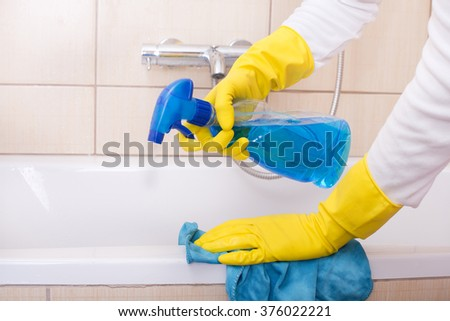 Close up of female hands with rubber gloves cleaning bathtub with cloth and liquid detergent from spraying bottle