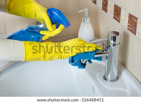 Close up of female hands with rubber gloves cleaning faucet and sink in bathroom with mop and detergent from spray bottle - stock photo