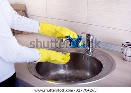 Close up of female hands with rubber gloves cleaning kitchen sink and faucet