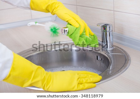 Close up of female hands with rubber gloves cleaning kitchen sink and faucet - stock photo