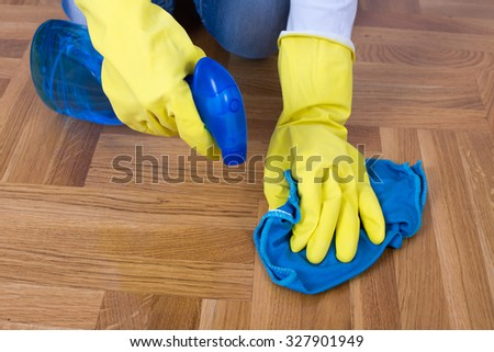Close up of female hands with rubber gloves cleaning parquet with detergent and cloth - stock photo