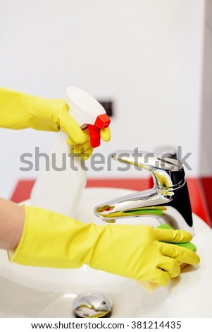 Close up of female hands with yellow rubber gloves spraying liquid detergent on tap and cleaning it with sponge. Spring cleaning - stock photo