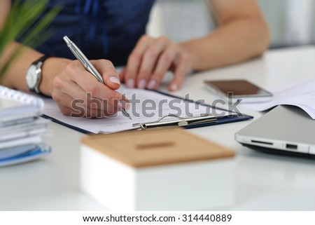 Close-up of female hands. Woman writing something and looking at mobile phone screen sitting at her office - stock photo