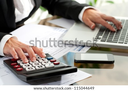 Close up of female hands working on calculator and laptop.