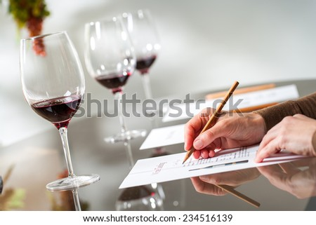 Close up of female hands writing notes at wine tasting. - stock photo