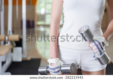 Close-up of  female holding barbells - stock photo