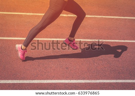 Close up of female jogger legs running on athletic track