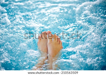 Close-up of female legs in hot tub - stock photo