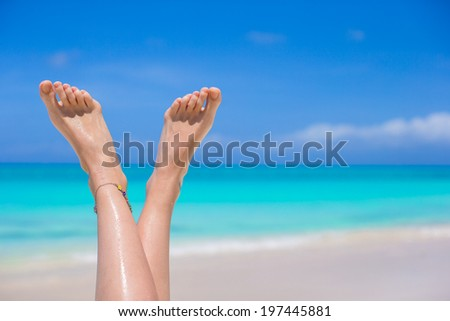 Close up of female legs on white sandy beach