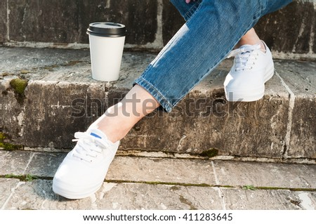 Close up of female legs wearing white sneackers and coffee on stone stairs outside in the park - stock photo