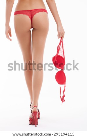 Close up of female legs with heeled shoes. The girl is showing her buttocks and red panties. She is holding bra in her right hand. Isolated on background - stock photo