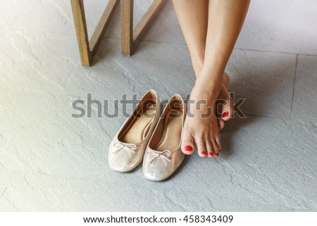 Close up of female legs with shoes under wooden table