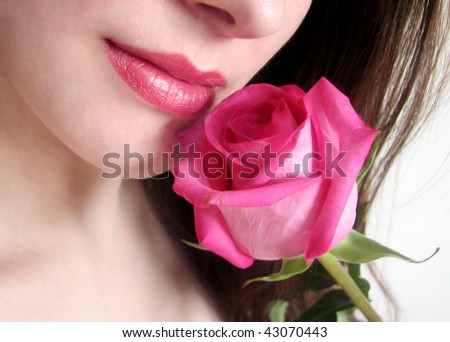 Close-up of female lips with pink rose - stock photo