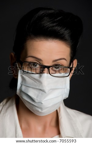 Close-up of female medical professional with face mask and glasses - stock photo