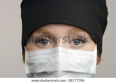 Close up of female medical staff wearing surgical mask and cap - stock photo
