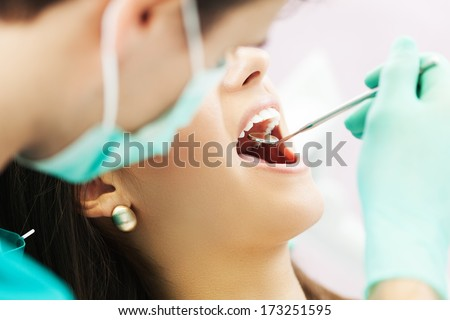 Close-up of female patient having her teeth examined by specialist  - stock photo