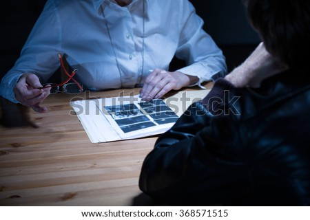 Close up of female police officer presenting evidence to suspect - stock photo