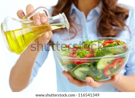 Close-up of female pouring oil into vegetable salad in glass bowl - stock photo