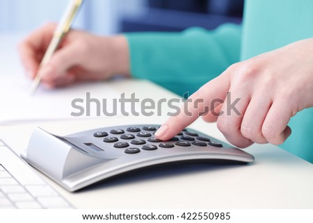 Close-up of female professional man working on business report while sitting at desk in office.  - stock photo