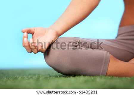 Close-up of female?s knee during meditation in pose of lotus with her legs crossed