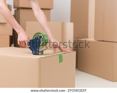 close-up of female sealing cardboard box with green duct tape - stock photo