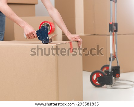 close-up of female sealing cardboard box with red duct tape - stock photo