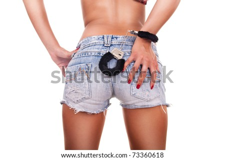 Close up of female sexy back dressed in jeans with handcuffs- isolated on white - stock photo