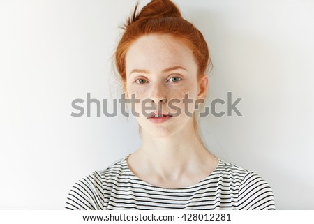 Close up of female teenager with healthy clean fresh skin with freckles wearing sailor shirt, looking at the camera. Portrait of student girl with red hair and blue eyes. Youth and skin care concept - stock photo