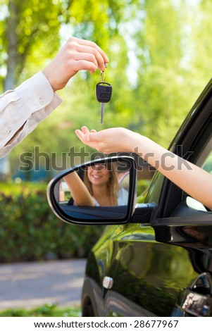 close up of female with arm outstretched taking car keys from man. Copy space - stock photo