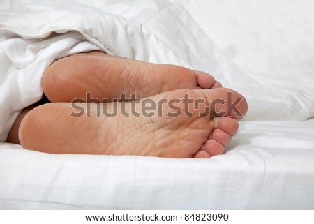 Close up of feminine feet in a bed - stock photo