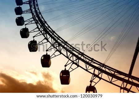 Close-up of ferris wheel at sunset. - stock photo
