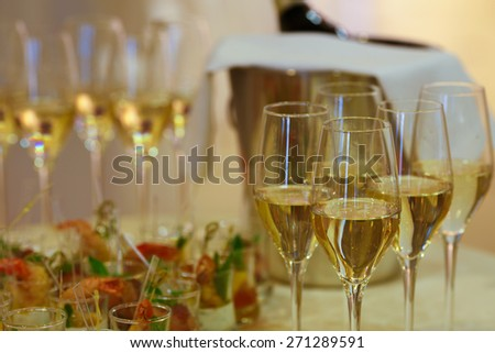 Close up of festive table with appetizers and drinks. Focus on a glass of champagne. Wedding, celebration, feast concept.