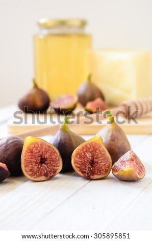 Close-up of figs, honey and cheese. Retro, vintage look. Selective focus - stock photo